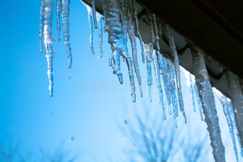 与垂悬从房子屋顶的冰冰柱的春天风景  库存图片