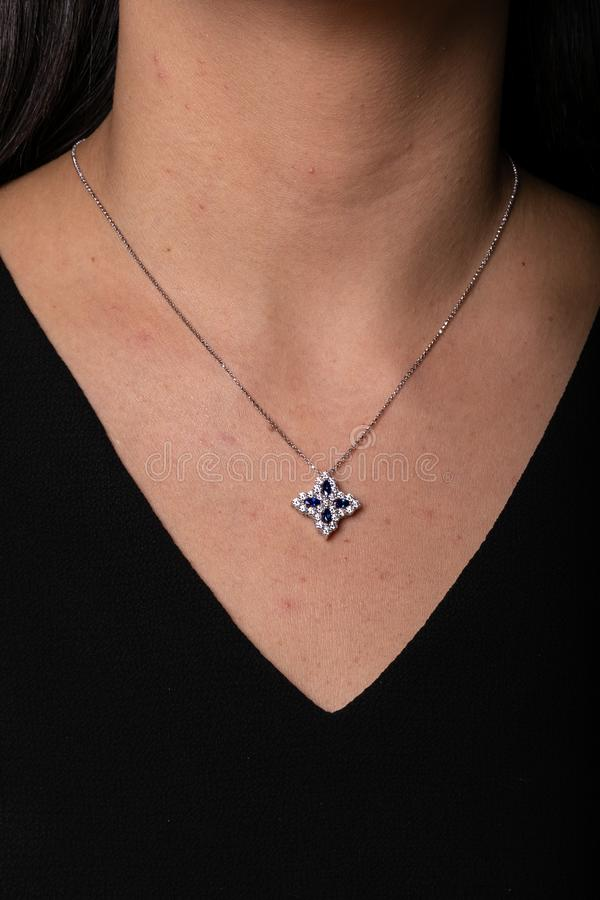 与垂饰的银色女性链子以与垂悬在他的脖子上的蓝宝石的一朵花的形式 库存图片