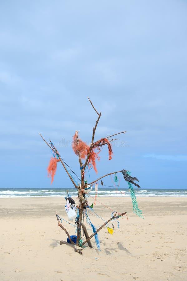 与垃圾树的风景空的海滩 免版税库存照片