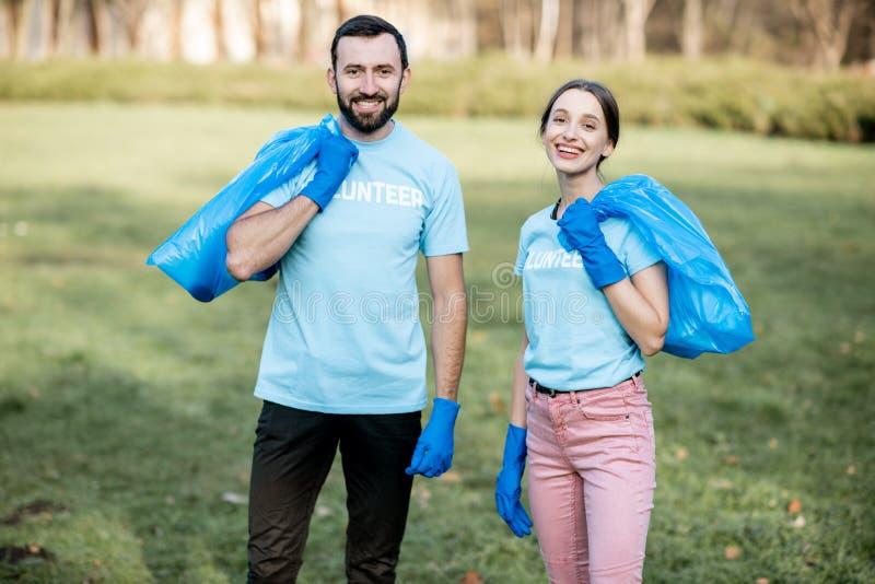 与垃圾袋子的志愿者画象在公园 库存照片