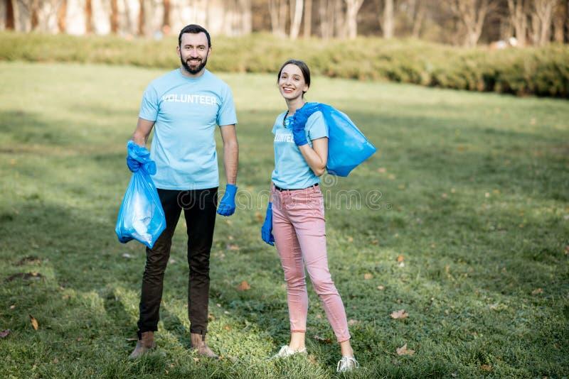 与垃圾袋子的志愿者画象在公园 免版税库存照片