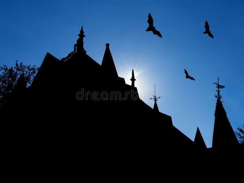 与城堡屋顶剪影的万圣夜背景有风标和飞行棒的 免版税库存照片