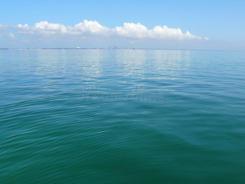 与城市地平线的海洋宽视图和在距离的白色云彩 库存图片