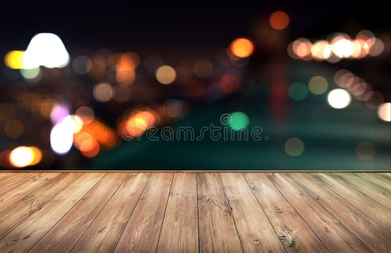 与城市的木桌点燃夜被弄脏的背景 库存照片