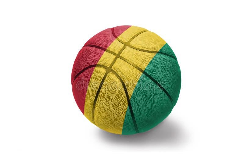 与基尼国旗的篮球球在白色背景的 库存图片
