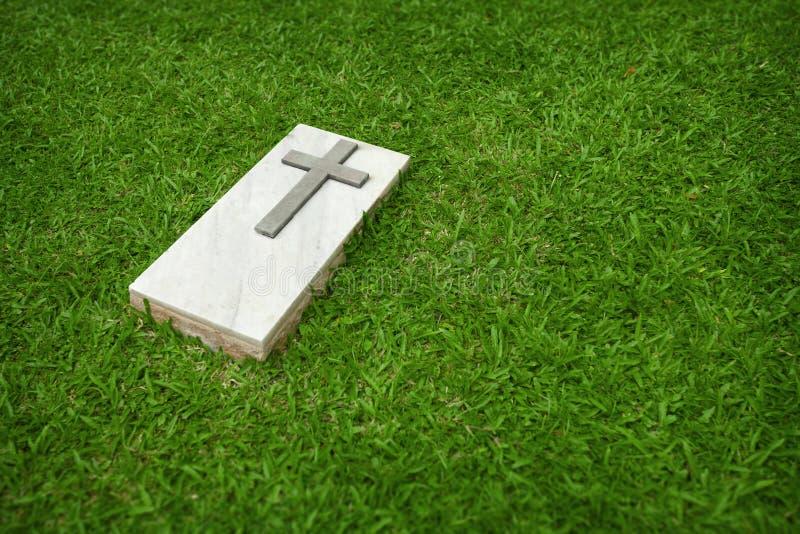 与基督徒十字架的大理石墓碑在绿色草坪 免版税库存照片