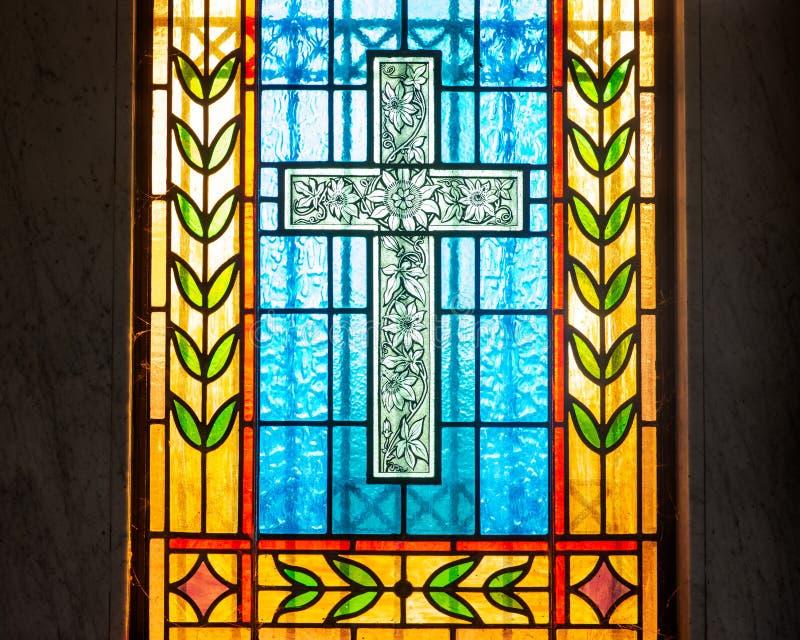 与基督徒十字架的污迹玻璃窗 免版税库存照片