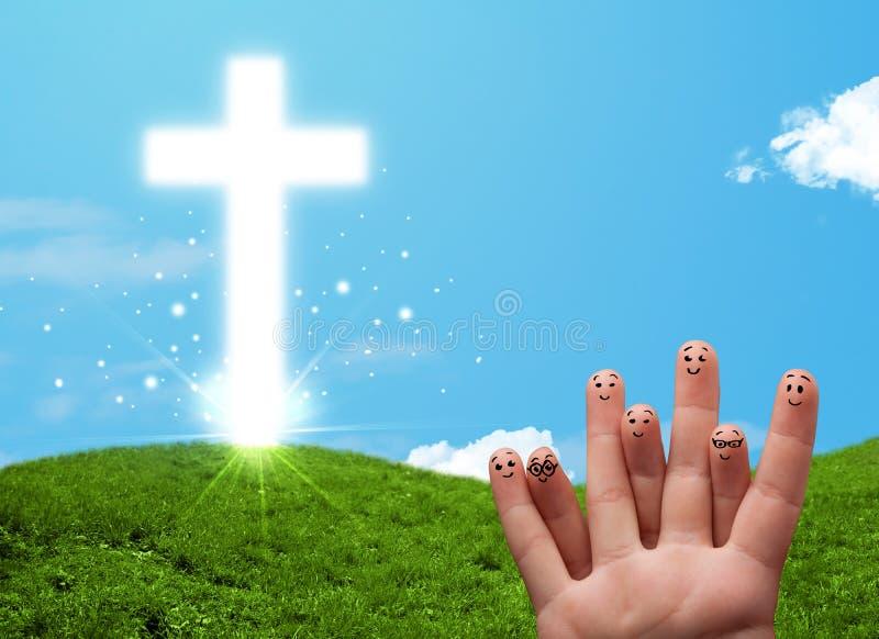 与基督徒宗教十字架的愉快的手指面带笑容 免版税图库摄影