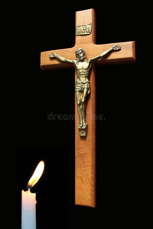 与基督的身体的木十字架有被点燃的蜡烛的 免版税库存图片