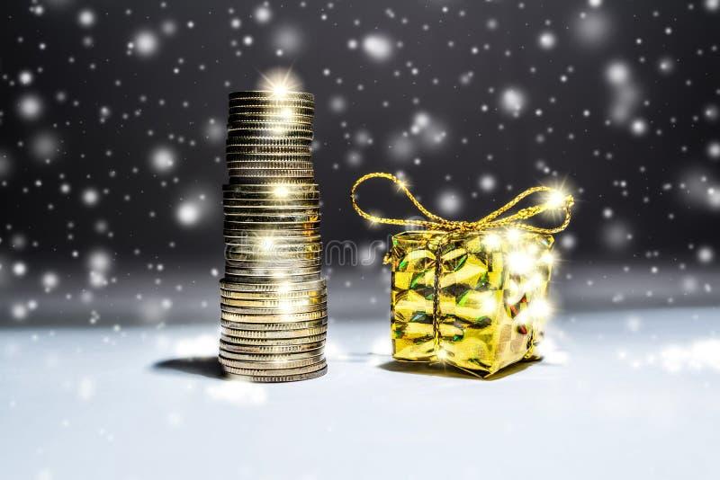 与堆的新年的静物画金币和有一件礼物的一个箱子在与落的雪的黑暗的背景 图库摄影