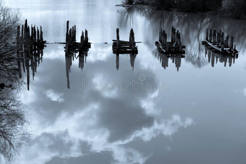 与堆的片段的美好的水风景老桥梁 免版税库存照片