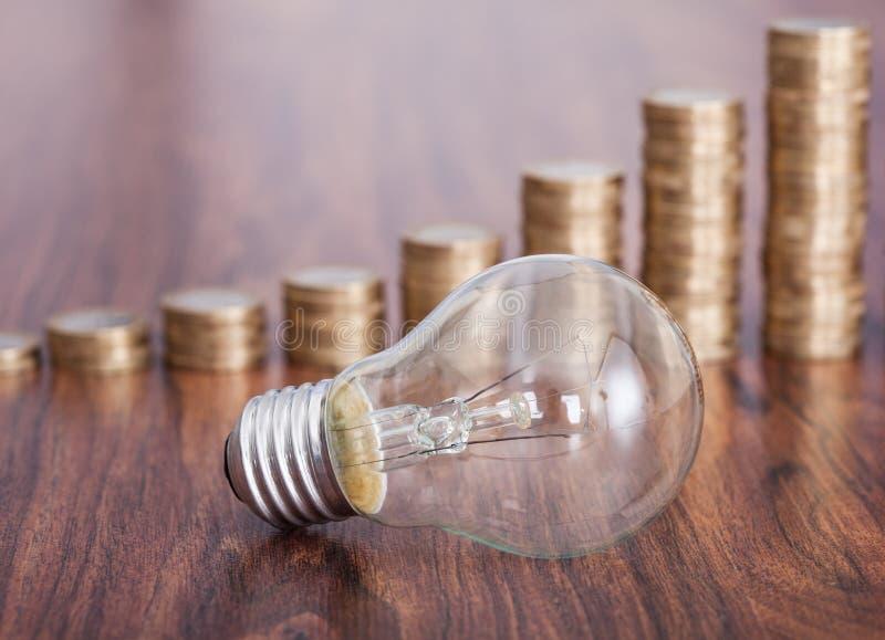 与堆的电灯泡硬币 图库摄影