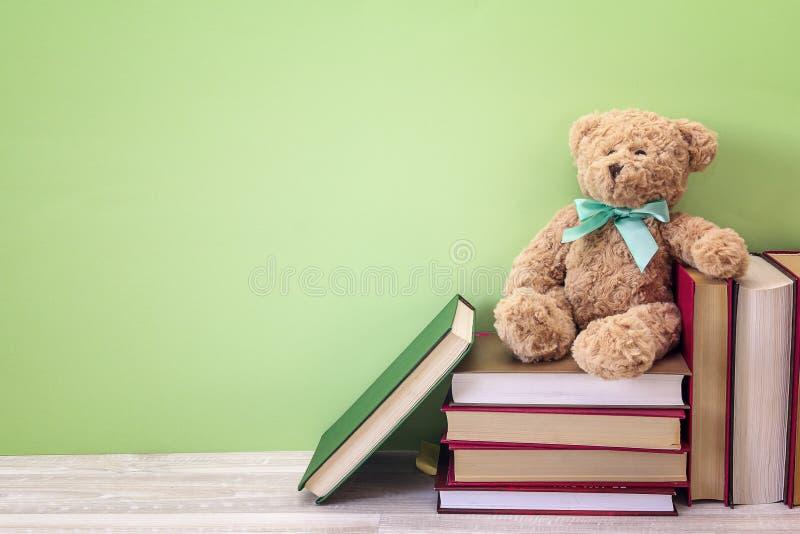 与堆的长毛绒熊在绿色背景的书 复制空间 库存图片