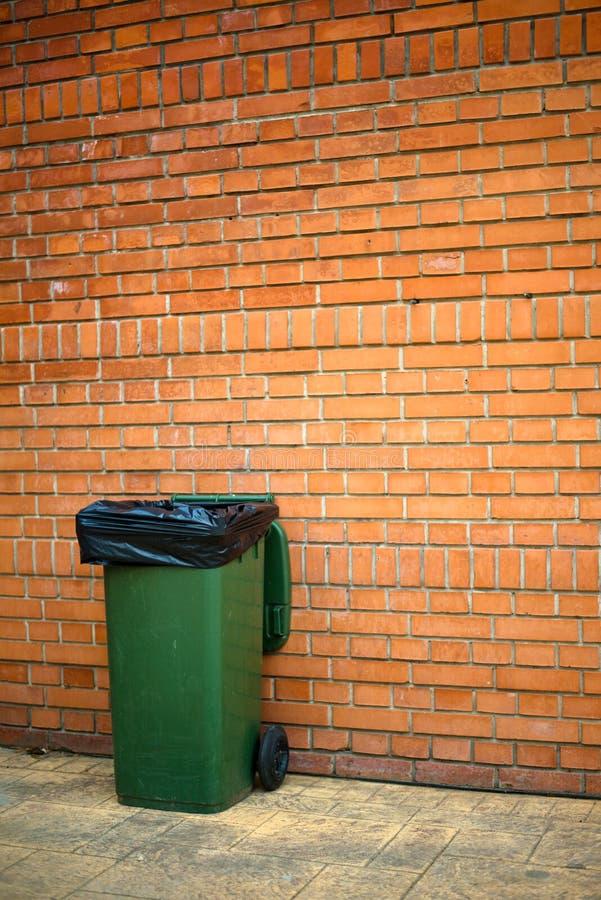 与塑料袋的绿色垃圾箱 免版税库存图片