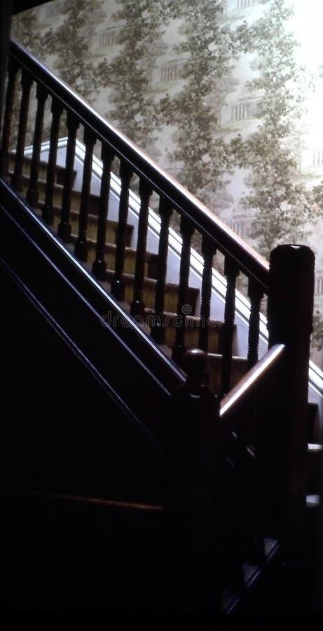 与墙纸墙壁的老木楼梯 免版税库存图片