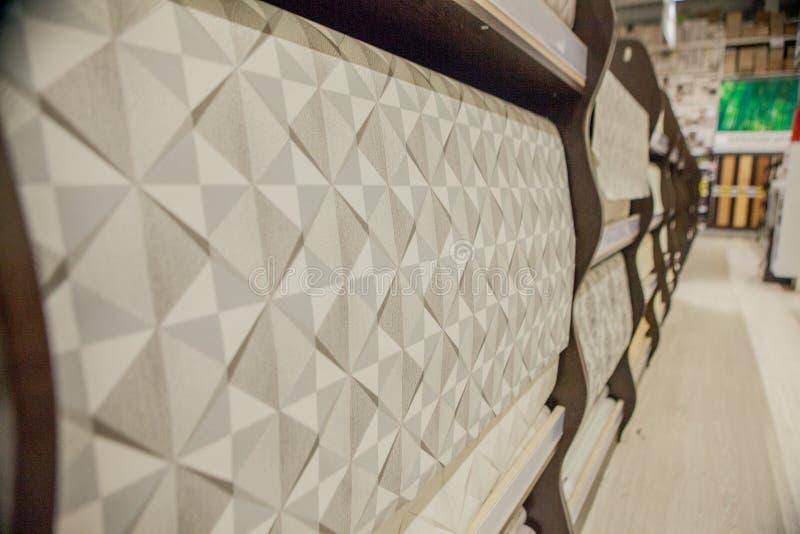 与墙纸的一种大选择的架子在商店 墙纸五颜六色的卷作为背景的 图库摄影