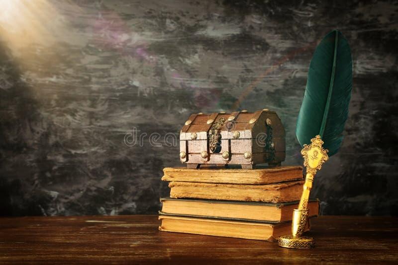 与墨水池、胸口和旧书的老羽毛纤管墨水笔在黑墙壁背景前面的木书桌 葡萄酒老牌 库存照片