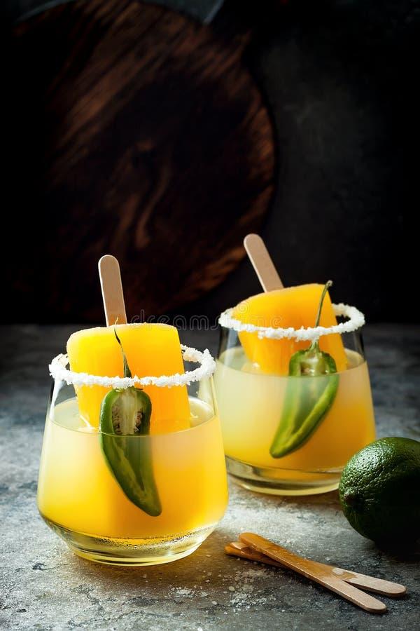 与墨西哥胡椒和石灰的辣芒果冰棍儿玛格丽塔酒鸡尾酒 Cinco de马约角党的墨西哥酒精饮料 免版税库存照片