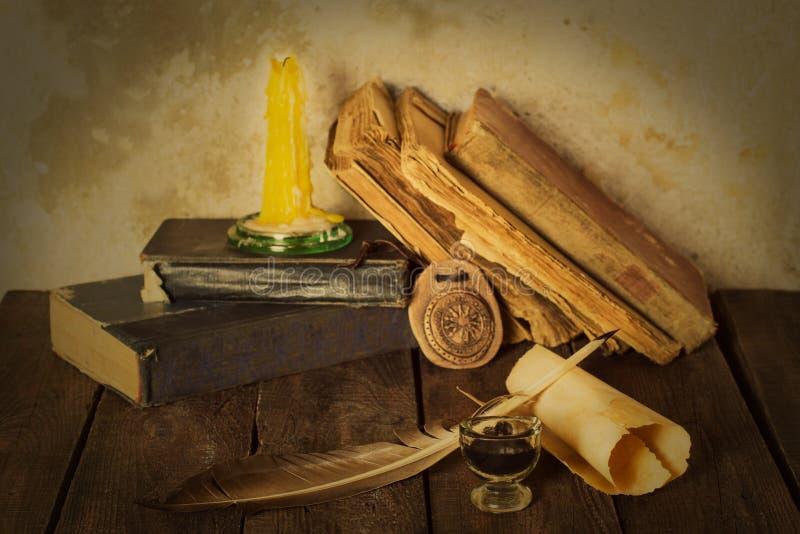 与墨水的旧书、蜡烛和羽毛护身符 免版税库存图片