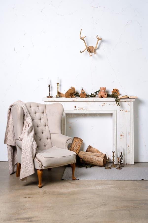 与壁炉、扶手椅子和圣诞节装饰的白色最低纲领派顶楼内部 库存图片