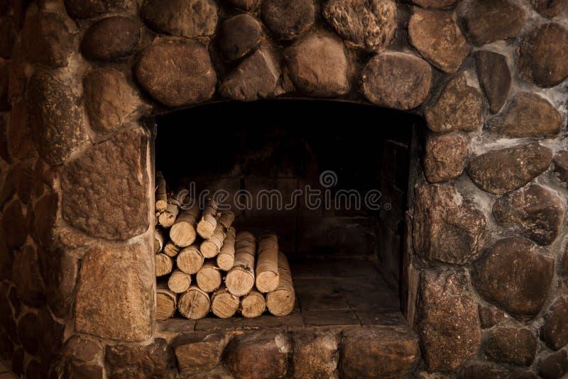 与壁炉边和日志的石壁炉 免版税库存照片