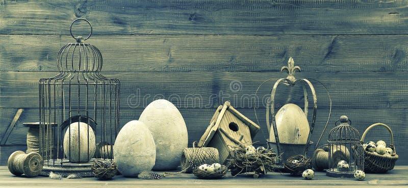 与复活节装饰、鸡蛋、巢和birdc的葡萄酒静物画 免版税库存照片