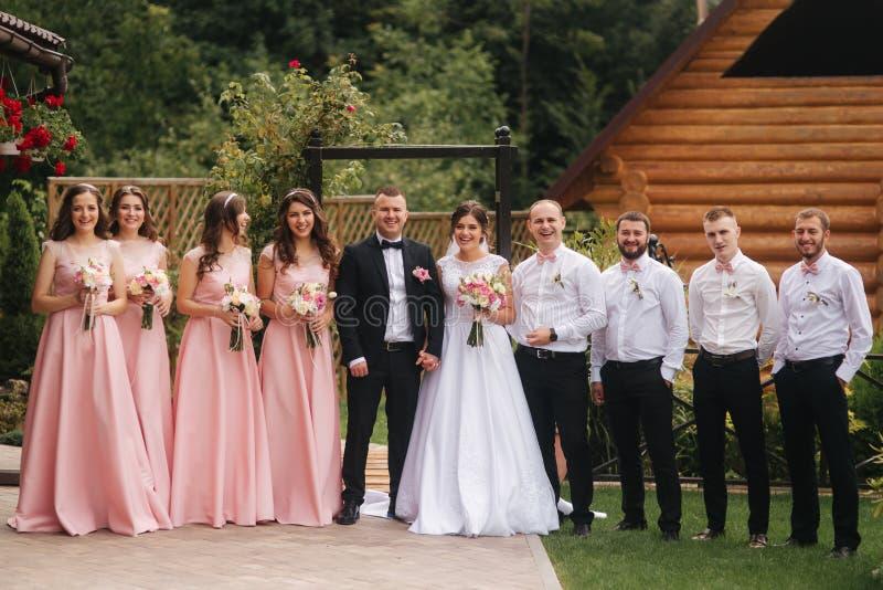 与外面男傧相和女傧相的新郎和新娘立场 亲吻的新婚佳偶和朋友拍手 o 图库摄影