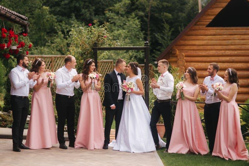 与外面男傧相和女傧相的新郎和新娘立场 亲吻的新婚佳偶和朋友拍手 o 库存图片