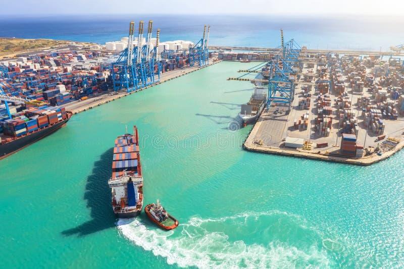 与多个容器风帆的货船到有工业起重机的港口海口里,卸载的 海上运输 免版税库存图片