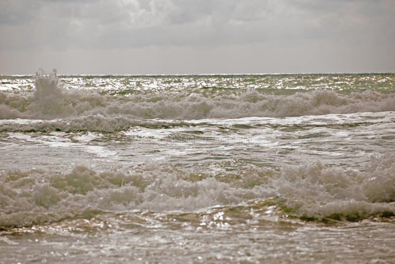 与多云天空和挥动的海海浪的风雨如磐的海景在湿棕色沙子 绿浪水以白色泡沫波浪和黑暗 免版税库存照片