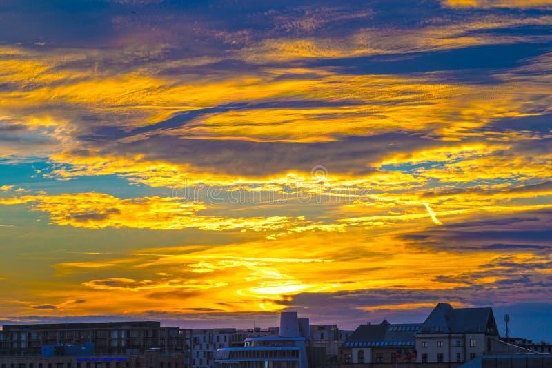 与多云天空的剧烈的淡黄色日落在科隆,德国 库存图片
