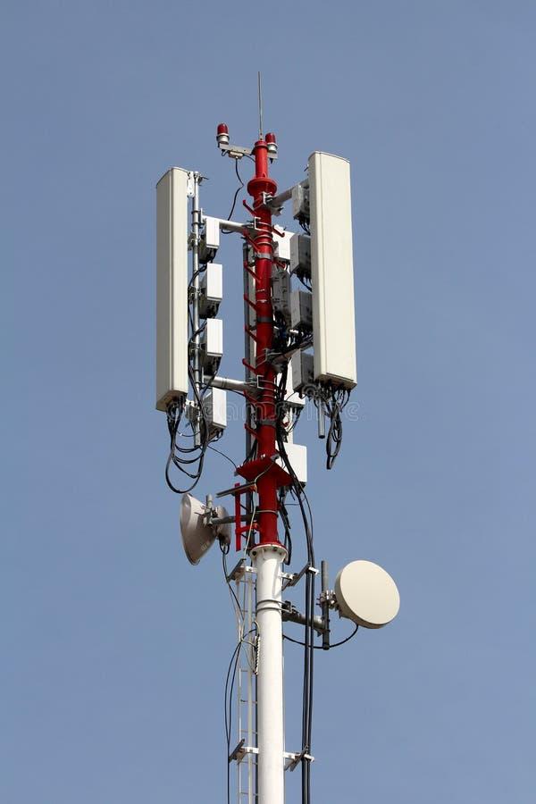 与多台在与清楚的天空蔚蓝的每边登上的手机发射机和天线的强的高红色和白合金杆 图库摄影
