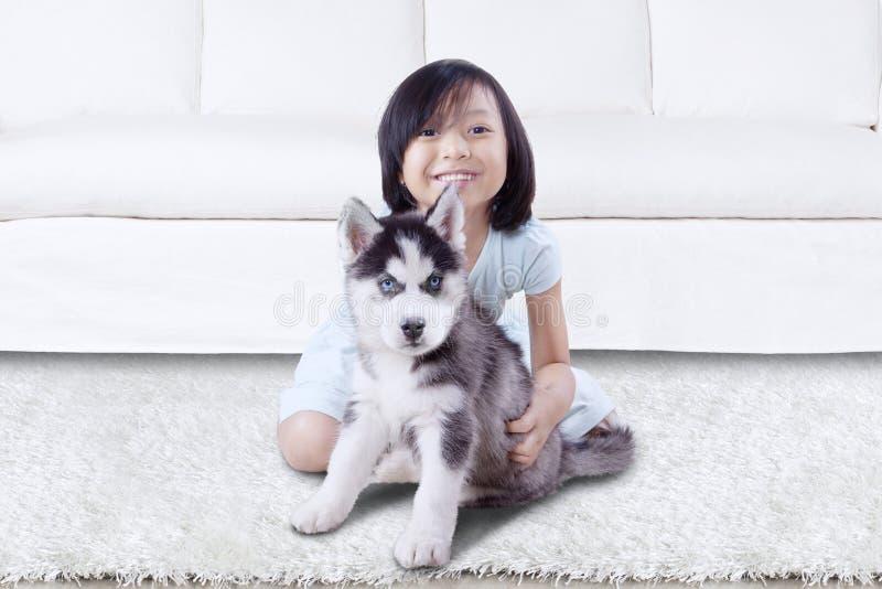 与多壳的小狗的小女孩戏剧在家 库存照片