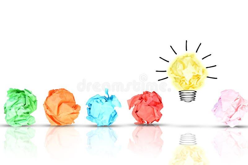 与多张五颜六色的被弄皱的纸的突破概念在一个黄色明亮的电灯泡附近的塑造了在白色backg的纸 免版税库存图片