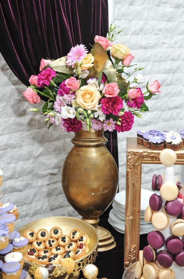 与多彩多姿的玫瑰的婚礼装饰在花瓶,柔和的淡色彩上色了杯形蛋糕、蛋白甜饼、松饼和macarons 免版税库存照片