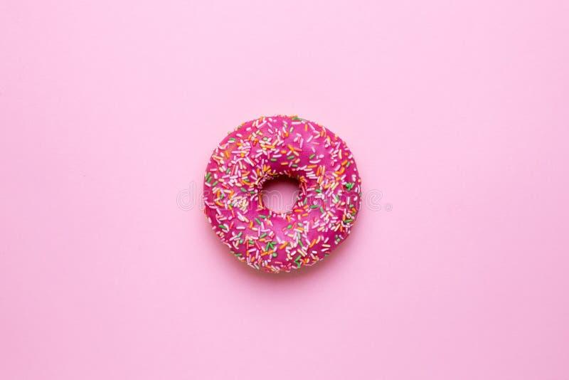 与多彩多姿的甜桃红色多福饼在平桃红色的背景洒放置 库存照片