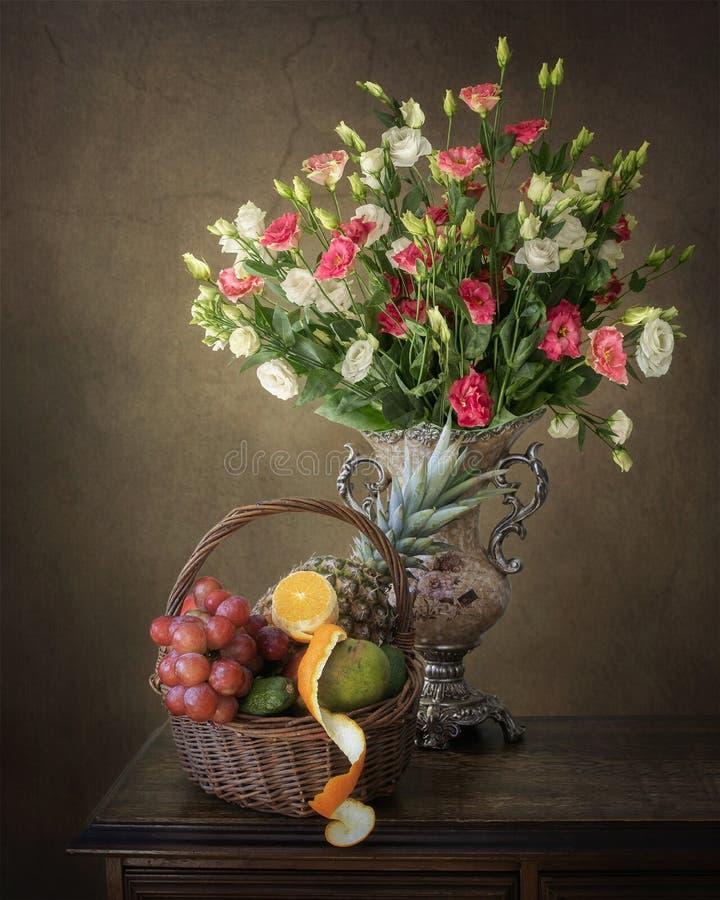 与多彩多姿的花和水果篮豪华花束的静物画  库存图片
