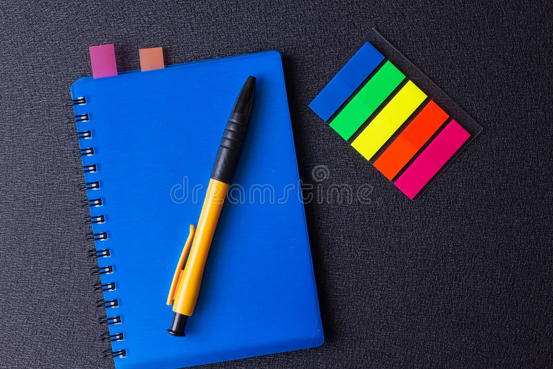 与多彩多姿的贴纸和笔的蓝色笔记薄 库存图片