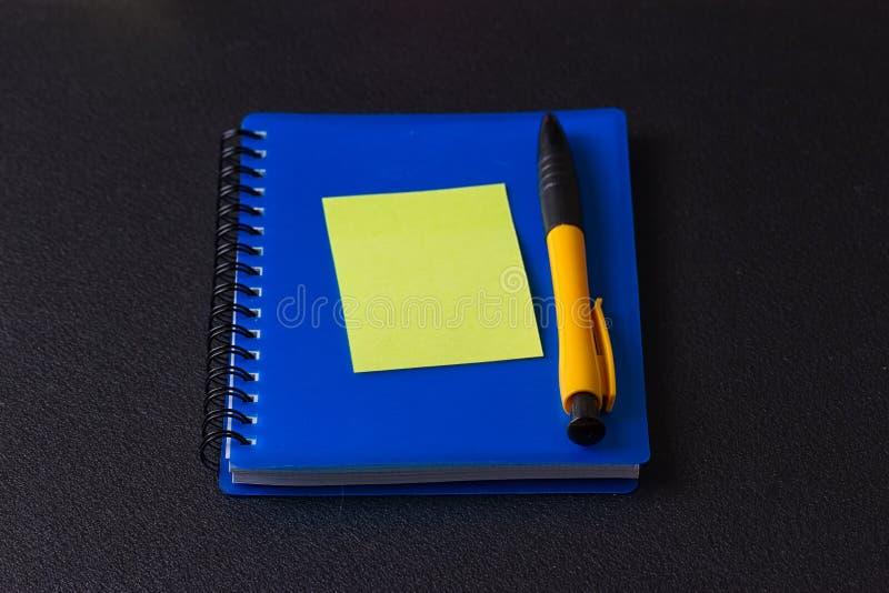 与多彩多姿的贴纸和笔的蓝色笔记薄 库存照片