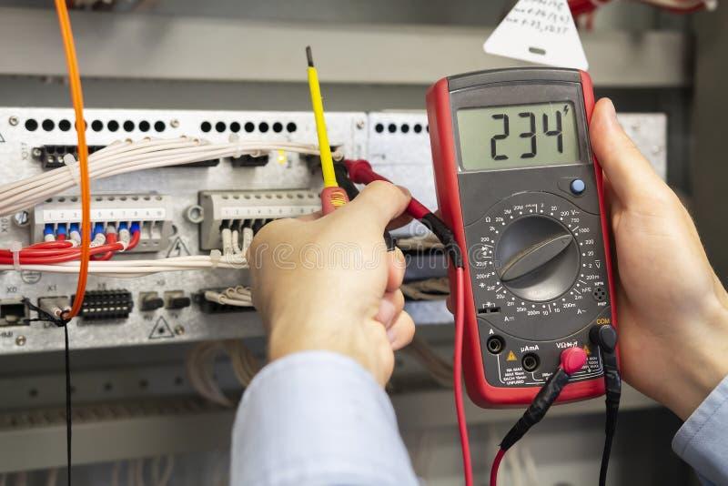 与多用电表测试器的电工测量 审查与多用电表探针的男性技术员Fusebox 库存照片