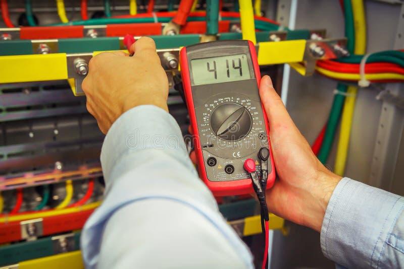 与多用电表特写镜头的工程师电措施电压 专业电工测量与测试器的电压 库存照片