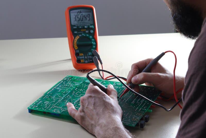 与多用电表的工程师测试电子元件 免版税库存照片