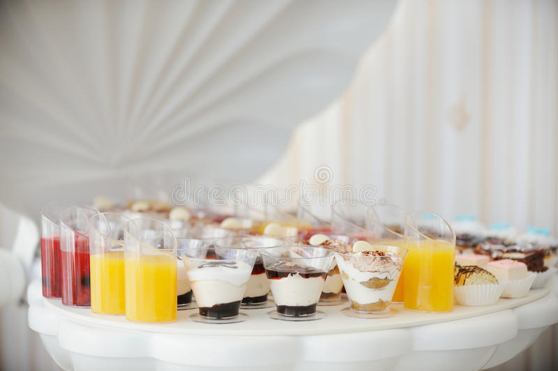 与多色的饮料,柔和的淡色彩的婚礼指叉上色了杯形蛋糕,蛋白甜饼 典雅和豪华事件安排 婚姻 免版税库存图片