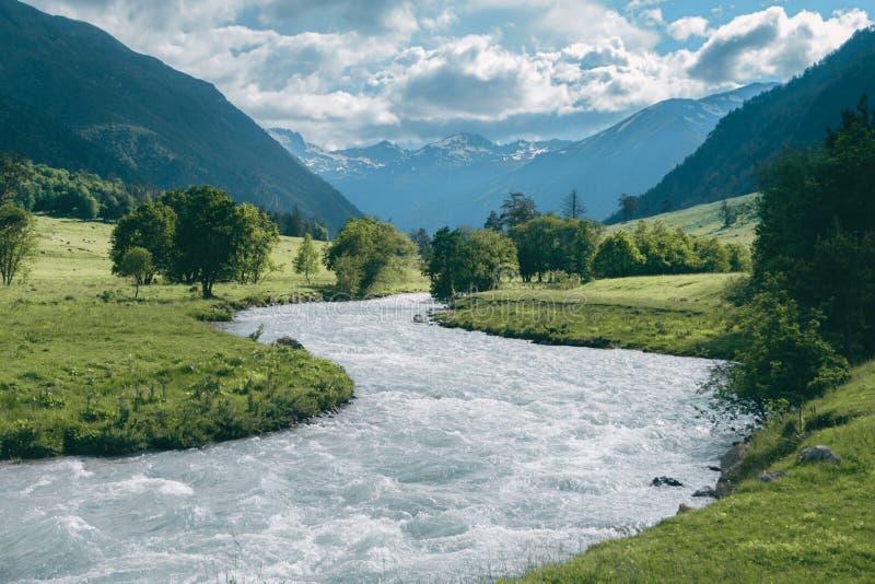 与多雪的山峰和多云天空的高地河风景在背景 免版税库存图片