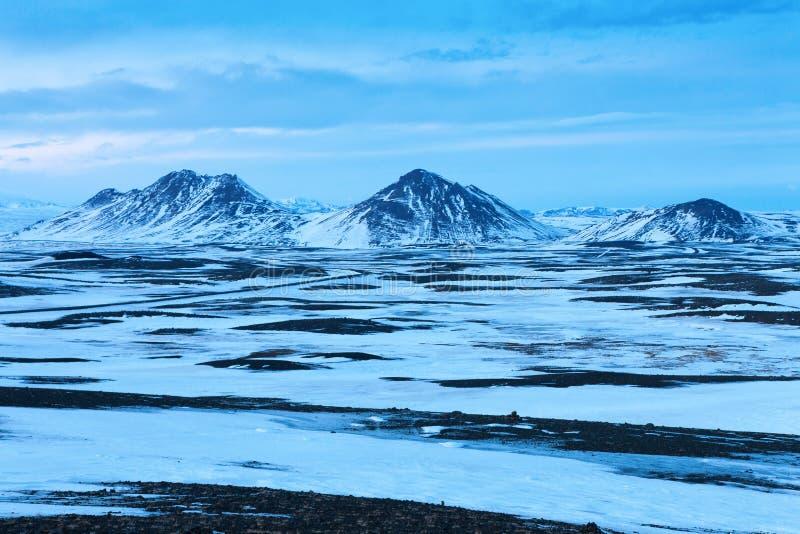 与多雪的山的典型的冬天风景在Egilsstadir和阿克雷里之间的背景中,在冰岛东北部 免版税库存照片