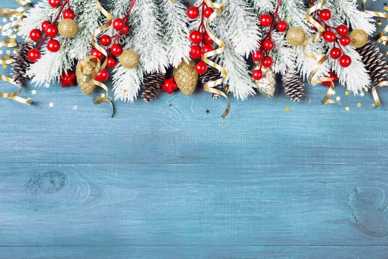与多雪的杉树和假日装饰的圣诞节背景在蓝色木台式视图 看板卡问候空间文本 库存照片