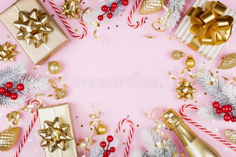 与多雪的杉树的圣诞节背景、礼物或者当前箱子、香槟和假日装饰在桃红色台式视图 平的位置 免版税库存照片
