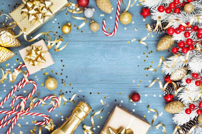 与多雪的杉树的圣诞节背景、礼物或者当前箱子、香槟和假日装饰在蓝色木台式视图 免版税库存图片