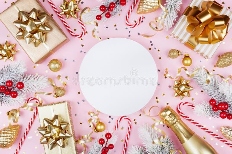 与多雪的杉树的圣诞节背景、纸空白、礼物或者当前箱子、香槟和假日装饰在桃红色淡色桌上 免版税库存照片