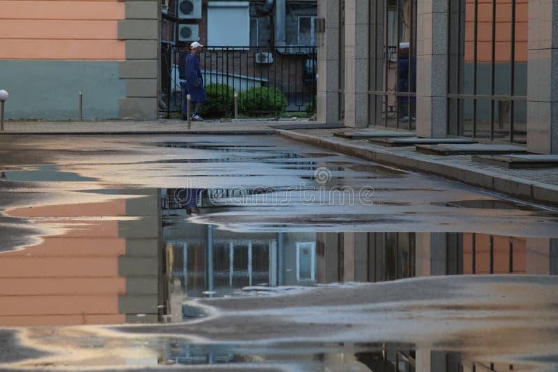 与大厦的水坑和元素的都市风景在日落的 图库摄影